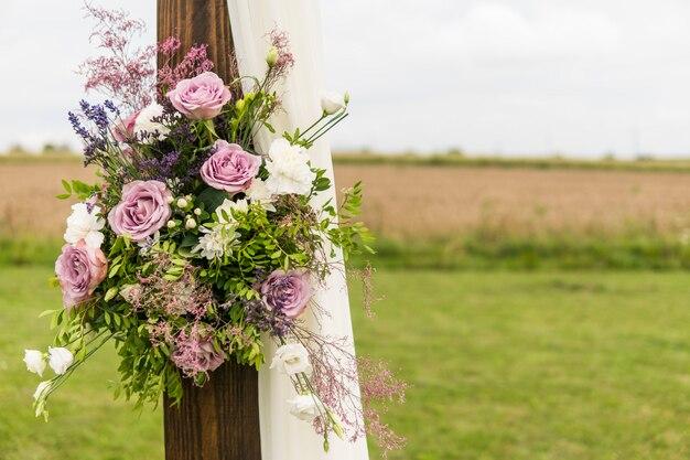 Kwiatowy drewniany łuk z białą tkaniną i świeżymi fioletowymi różowymi białymi kwiatami z zielonymi liśćmi na rustykalnej ślubie.