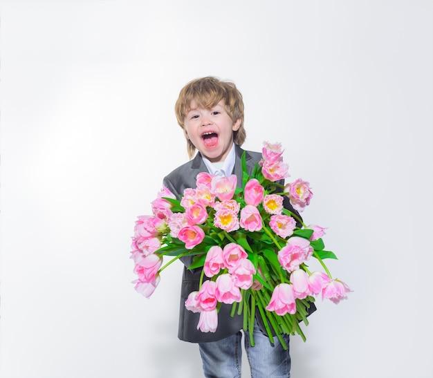 Kwiatowy prezent uśmiechający się elegancki mały chłopiec z bukietem tulipanów ślubna koncepcja prezent dla mamy stylowy