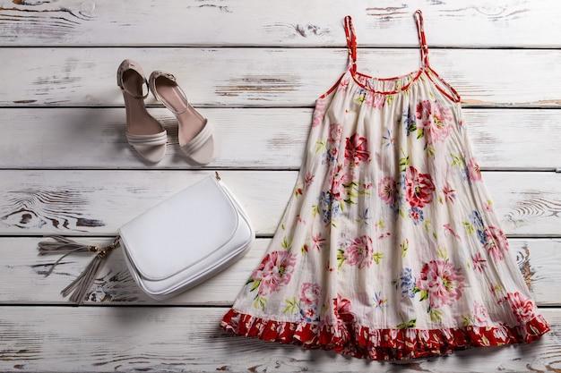 Kwiatowy sarafan i obuwie. sarafan i buty na gablocie. prosty damski strój na lato. ubiór z lekkiej tkaniny.