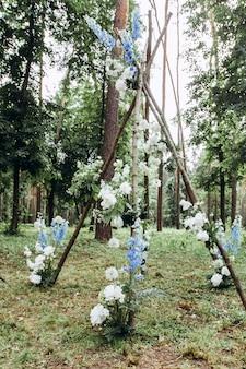 Kwiatowy tipi pod łukiem na piękny ślub w plenerze