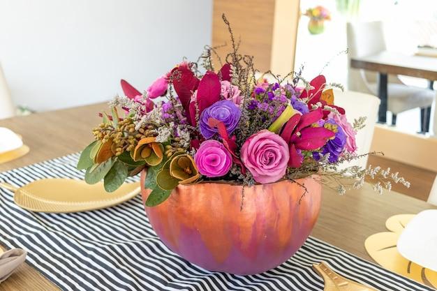 Kwiatowy układ róż wewnątrz dyni ozdobiony na inne halloween