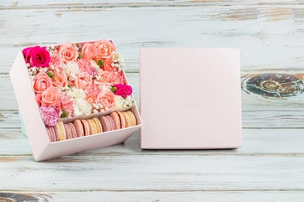 Kwiatowy układ różowych róż z makaronikami w różnych kolorach