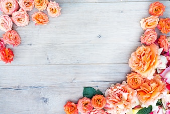 Kwiatowy wzór, rama wykonana z róż na drewniane tła. Płaski lay, widok z góry.