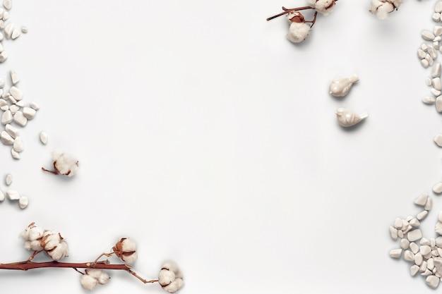 Kwiaty bawełny, morskie kamienie i dwa małe ceramiczne ptaszki