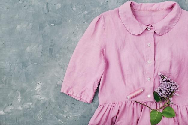 Kwiaty bzu i letnia sukienka w pastelowym różu