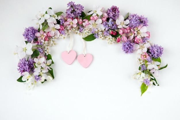 Kwiaty czeremchy, bzu i jabłoni wyłożone łukiem i dwoma różowymi sercami