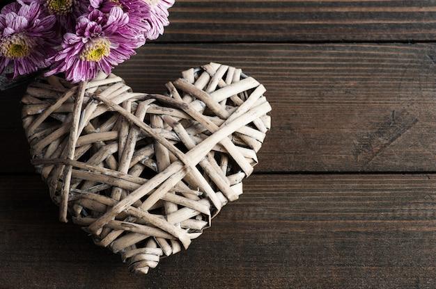 Kwiaty daisy i ozdobne wiklinowe serce