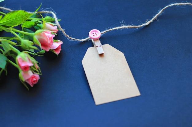 Kwiaty, dekoracyjne clothespins i papier do notatek na ciemnym tle. pojęcie gratulacje na wakacje