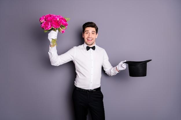 Kwiaty dla pani! zdjęcie przystojnego mężczyzny pokazującego trzymającego czarnego cylindra, który dostaje świeże piwonie od wewnątrz nosić białą koszulę muszkę spodnie na białym tle szary kolor ściana