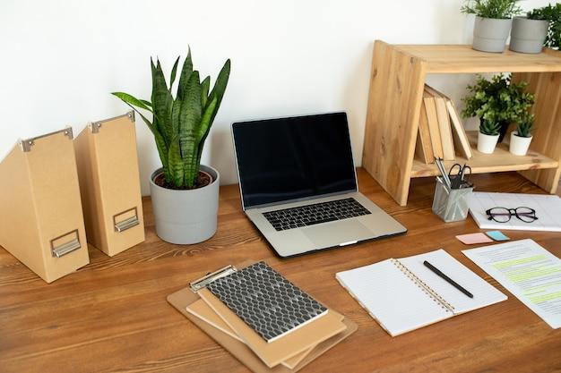 Kwiaty doniczkowe na półce i stole, laptop, zeszyty, papier, długopis i foldery na stanowisku pracy przy ścianie