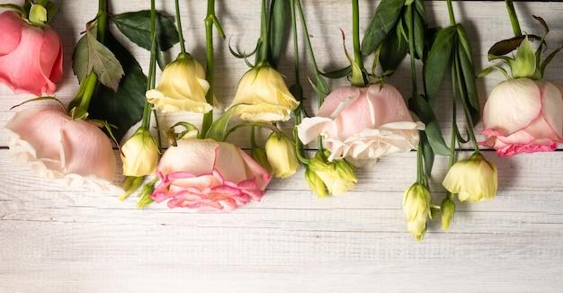 Kwiaty eustoma i różowe róże na powierzchni drewnianych w stylu vintage.