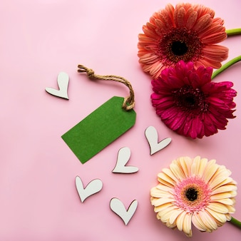 Kwiaty gerbera, drewniane serduszka i zielona papierowa metka na różowym pastelowym tle. widok z góry