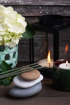 Kwiaty hortensji w wazonie i zapalone świece