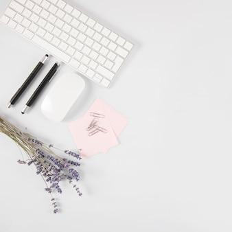 Kwiaty i artykuły papiernicze w pobliżu klawiatury i myszy
