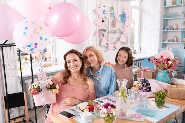 Kwiaty i balony. szczęśliwa rozpromieniona kobieta czuje się wesoła, trzymając ładne kwiaty ozdobione balonami powietrznymi