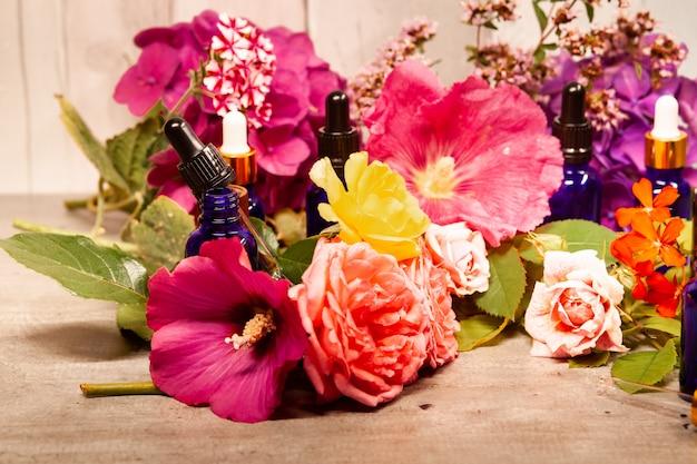 Kwiaty i butelki olejków eterycznych do aromaterapii