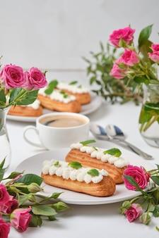 Kwiaty i eklery ozdobione kremem i miętą na białym stole. deser na romantyczną randkę. ciasta na święta.