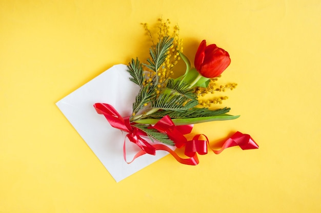 Kwiaty i koperta w kartkę z życzeniami