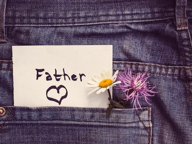 Kwiaty i papierowa notatka ze słowem ojciec
