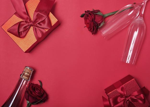 Kwiaty i prezenty pudełka na czerwoną butelkę szampana i okulary