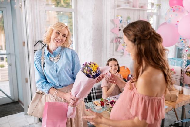 Kwiaty i prezenty. stylowa blondyneczka przychodząca do piekarni z kwiatami i prezentami dla ciężarnej koleżanki