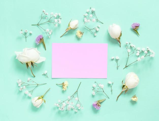 Kwiaty i różowy papier na jasnozielonym tle widok z góry