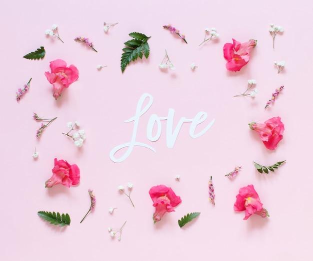 Kwiaty i słowo love na jasnoróżowym widoku z góry