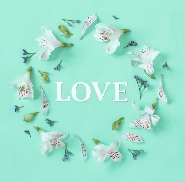 Kwiaty i słowo miłość na jasnozielonym tle widok z góry