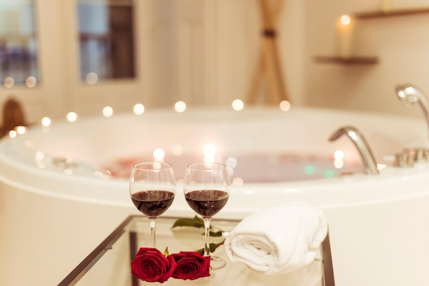 Kwiaty i szklanki napoju w pobliżu wanny spa z wodą i palenie świec na krawędziach