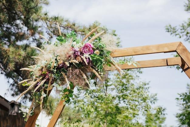 Kwiaty i zieleń na pięknym drewnianym łuku ślubnym