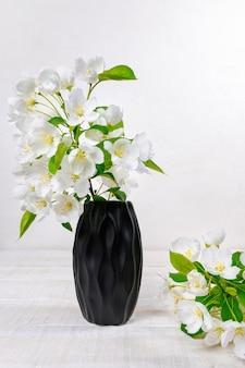 Kwiaty jabłoni w czarnym wazonie na białym drewnianym stole