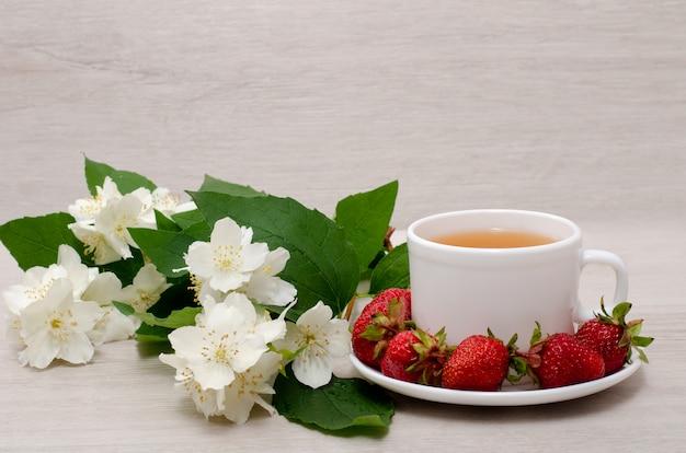 Kwiaty jaśminu, biały kubek z herbatą, truskawki, zbliżenie