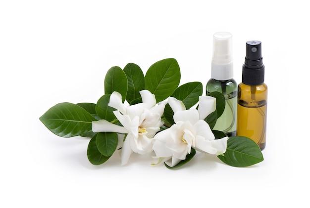 Kwiaty jaśminu cape i wyodrębnione w butelce z rozpylaczem na białym tle.