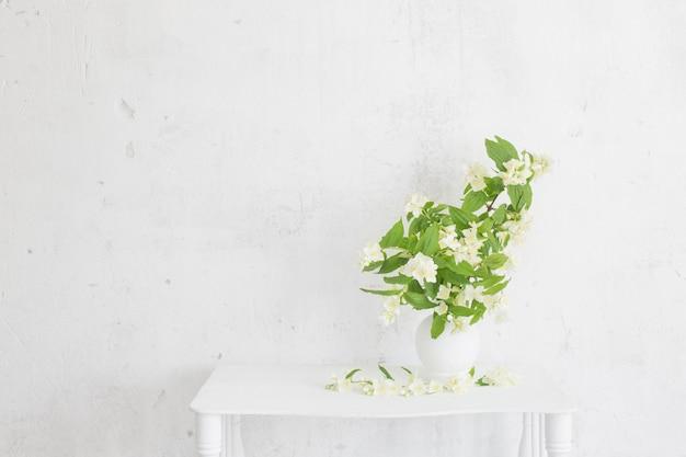 Kwiaty jaśminu w wazonie na tle starej ściany