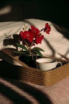 Kwiaty kawy i pocztówka na tacy na łóżku