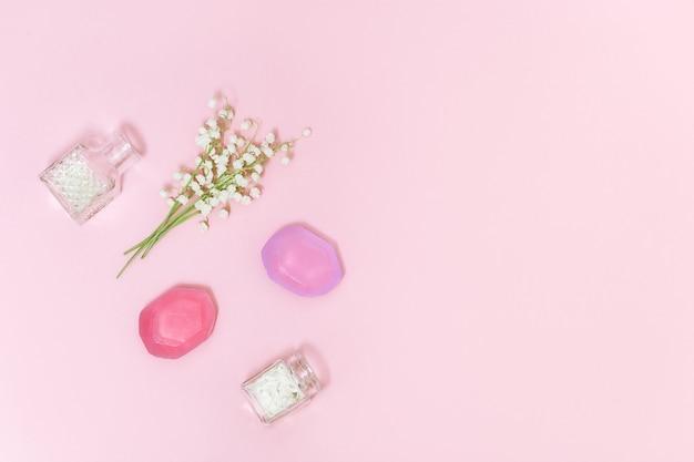 Kwiaty konwalii i pachnące mydło na miękkim różowym tle