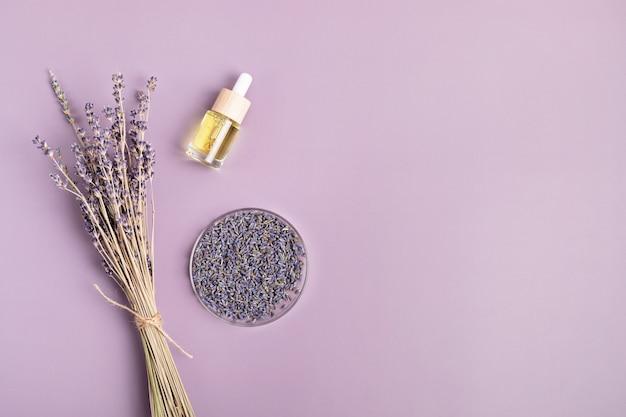 Kwiaty lawendy i ziołowy olejek eteryczny na fioletowym tle. naturalny zabieg upiększający, relaksacyjny, antystresowy. płaski układanie, widok z góry