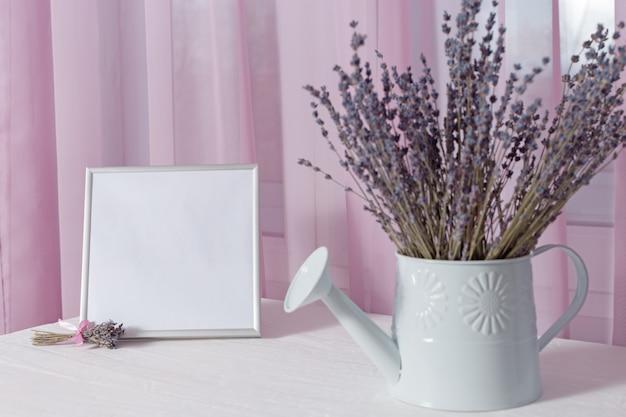 Kwiaty lawendy w konewce i ramce na zdjęcia o oknie