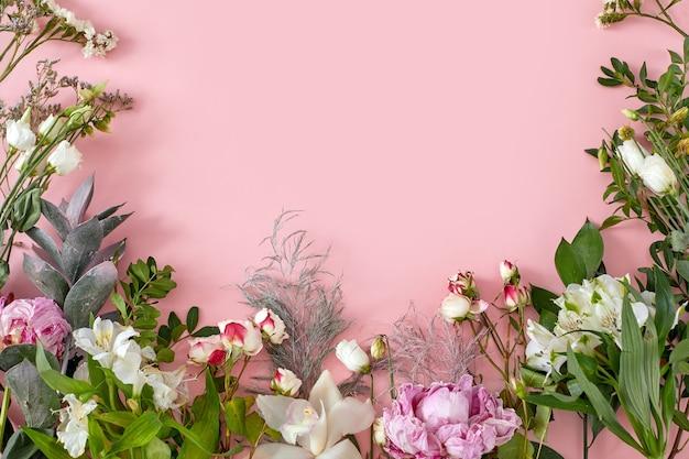 Kwiaty leżą na różowym papierze, tworząc florystyczną przestrzeń do kopiowania