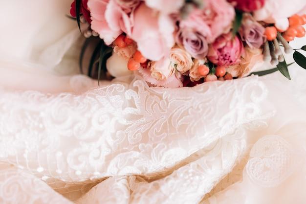 Kwiaty leżą w pobliżu sukni ślubnej