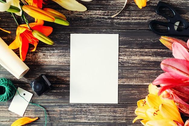 Kwiaty lilie, nożyczki, atrament i biały pusty arkusz na drewnianym stole. układ na kartkę z życzeniami