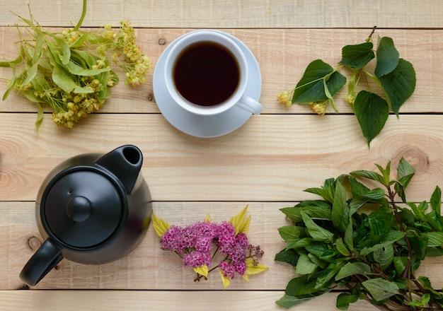 Kwiaty lipy oraz herbata i zielona mięta na jasnym drewnie. widok z góry