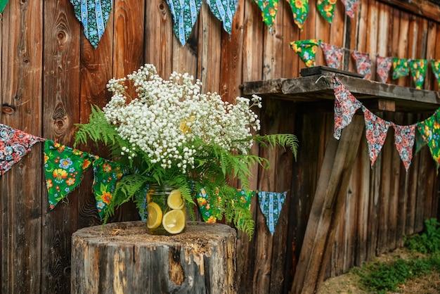 Kwiaty łyszczec z plastrami pomarańczy na tle drewnianej szopy z flagami