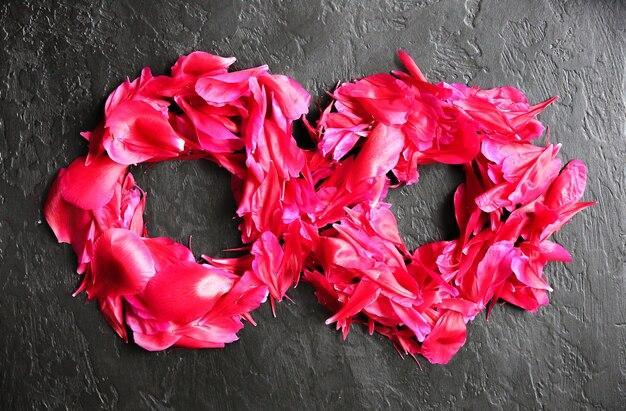 Kwiaty na czarnym tle. numer osiem z płatków piwonii. pozdrowienia z okazji międzynarodowego dnia kobiet. pomysł na ogłoszenie lub zaproszenie.