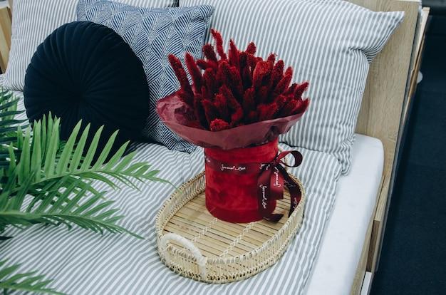 Kwiaty na łóżku w domu na rustykalnej drewnianej tacy do serwowania