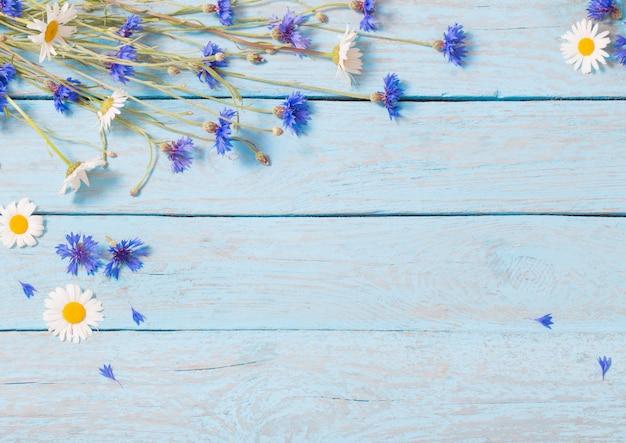 Kwiaty na niebieskiej drewnianej przestrzeni