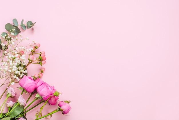 Kwiaty na różowym tle z pustym miejscem na tekst. widok z góry, płaski układ.
