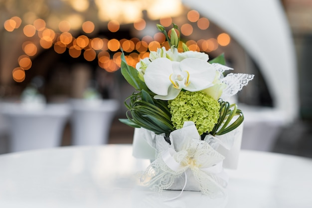 Kwiaty na stole w restauracji na świeżym powietrzu. wnętrze letniego tarasu kawiarni. nakrycie stołu na przyjęcie weselne lub wydarzenie. skopiuj miejsce na tekst.