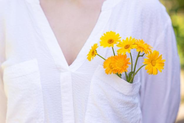 Kwiaty nagietka w kieszeni białej bluzki na dziewczęcej piersi.