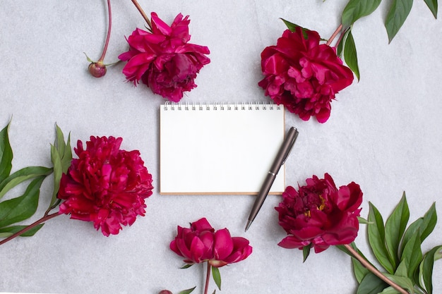 Kwiaty piwonii i pusty notatnik do planowania lub życzeń na kamieniu.